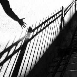 Фотография теней забора и руки